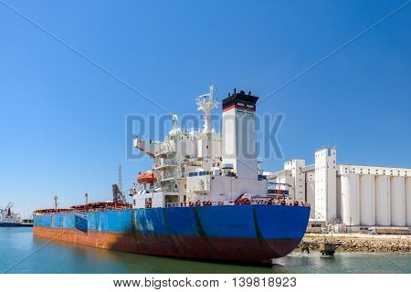 Bulk carrier ship unloading in the port