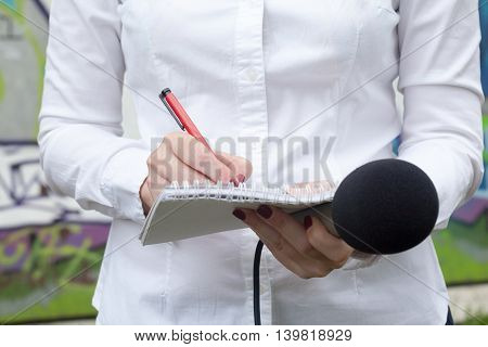 Female reporter or journalist at news conference writing notes and holding microphone