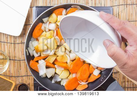 Chef pouring soup to the pan for cooking Japanese pork curry / cooking Japanese pork curry paste concept