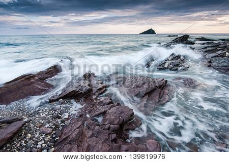 Stormy And Dramatic Clouds Over Rocky Beach