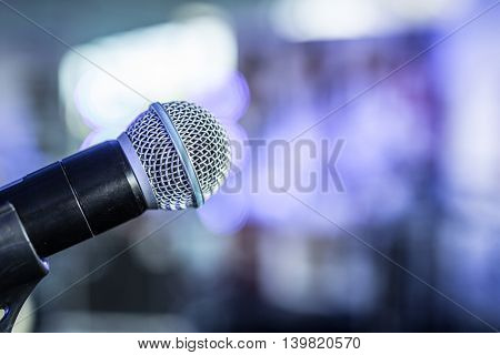 Closeup shot of microphone. Blurred lights on the background.