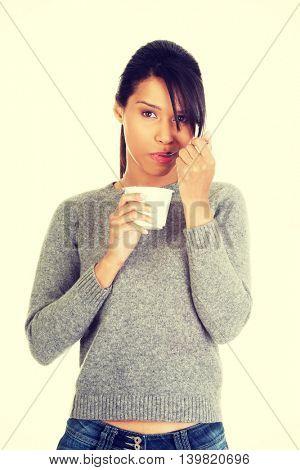 Young woman eating yogurt as healthy breakfast or snack.