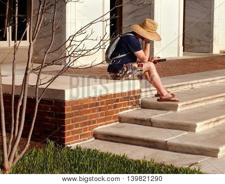 A young man in casual attire sits on the stairs outside a building reading text messages or emails on a cell phone.