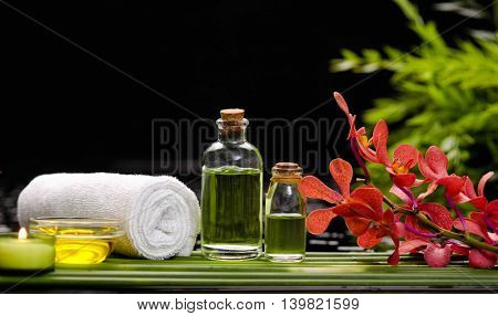 spa concept â??red orchid and ,stones , towel,candle on green long leaf