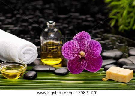 Pink orchid with candle oil ,soap ,towel on green plant on wet background