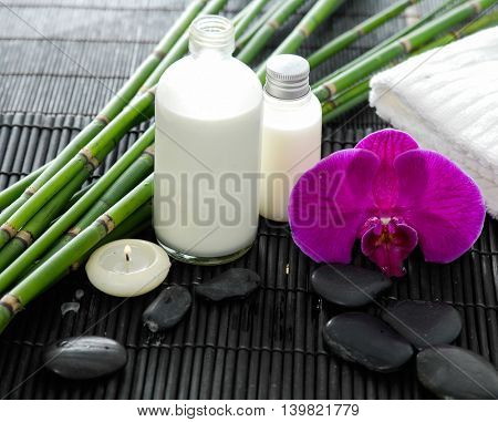 Spa setting with candle on towel ,stones ,grove on mat