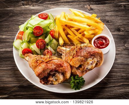 Roasted turkey legs with chips and vegetables