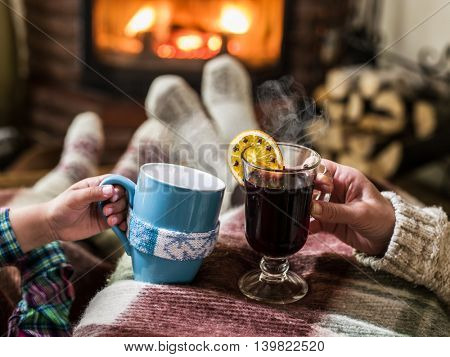 Warming and relaxing near fireplace. Mother and daughter with the cups of hot drink in front of fire.