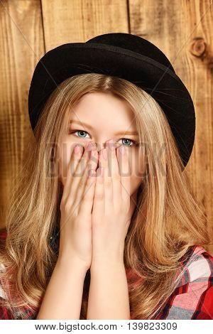 Pretty smiling girl wearing retro bowler hat over wooden background. Studio shot.