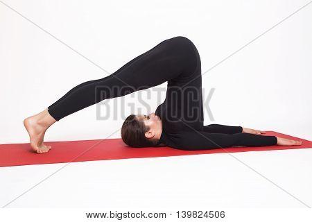 Beautiful athletic girl in a black suit doing yoga. halasana asana - plow pose . Isolated on white background.