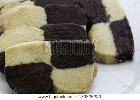 Homemade chocolate and vanilla checkerboard cookies on white plate