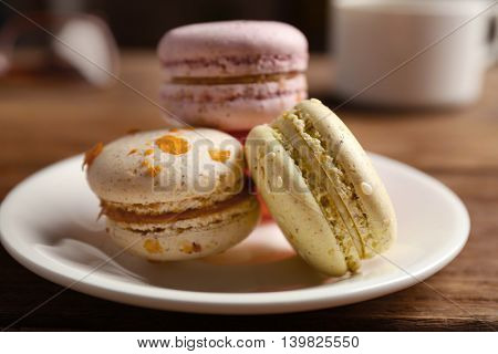 Heap of tasty macaroons in white plate on wooden table