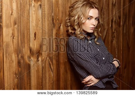 Casual teen girl sitting by a wooden wall. Youth style, fashion.