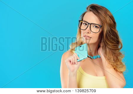 Pretty young woman holding her smartphone over blue background. Beauty, fashion. Modern telecommunications.