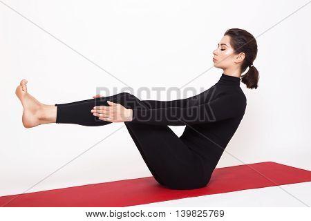 Beautiful athletic girl in a black suit doing yoga. naukasana asana - boat pose . Isolated on white background.
