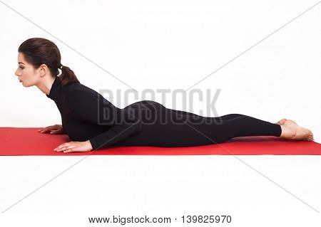 Beautiful athletic girl in a black suit doing yoga. bhujangasana asana - cobra pose . Isolated on white background.