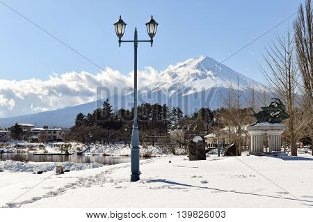 Snow covered Mt Fuji with a park and an ornate lamppost in the foreground.  Mt Fuji (Fujisan) is Japans highest peak.