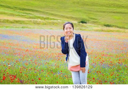 Chinese girl in the middle of the field of multi-colored flowers smiles and makes the sign of victory.
