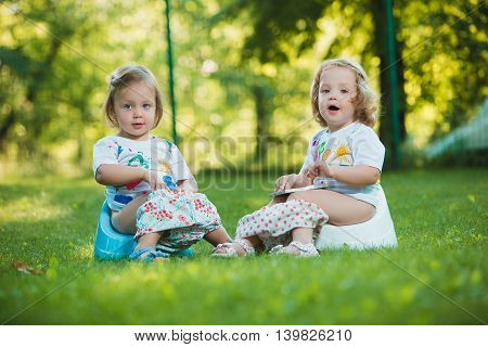The two little baby girls two-year old hanging upside down against green grass