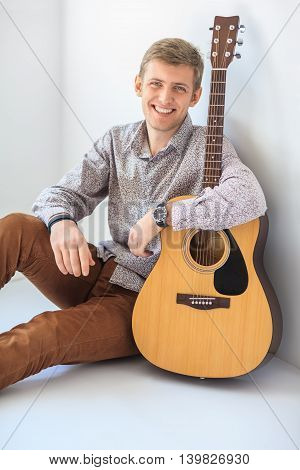 Portrait Of Happy Handsome Man With Guitar