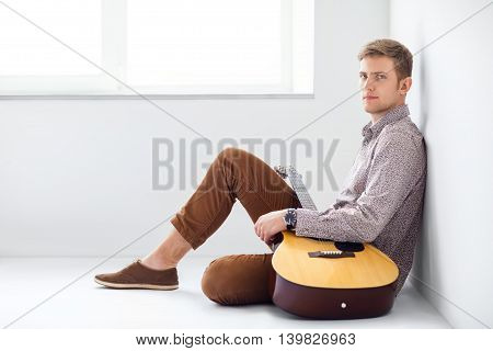 Portrait Of Handsome Man With Guitar Siting On Floo
