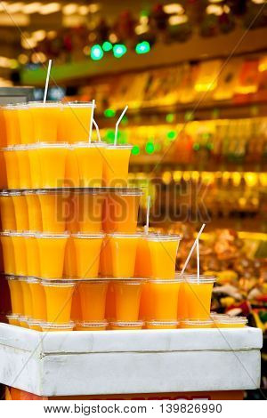 Many plastic glasses with orange juice on stall shop