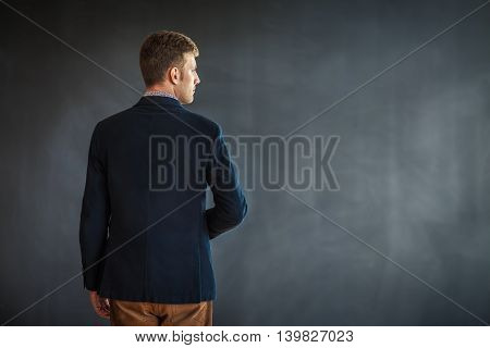 Rear View Of Young Man Standing Against Grey Wall Background
