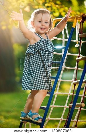 The little baby girl playing at outdoor playground against green grass