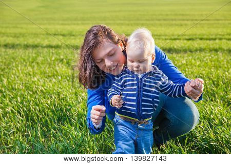 Mother and baby having fun, playing on green field