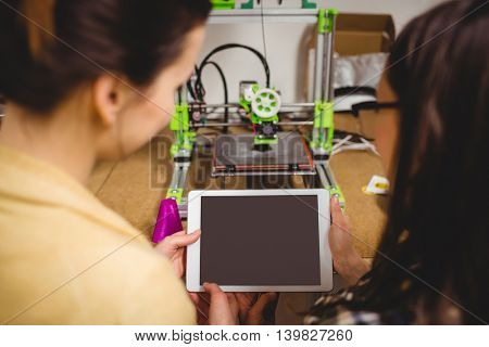 Close-up of graphic designers interacting using digital tablet in office