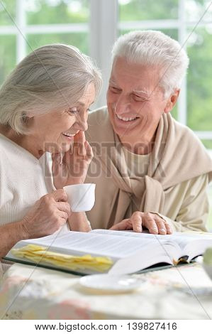 happy Senior couple drinking tea with book