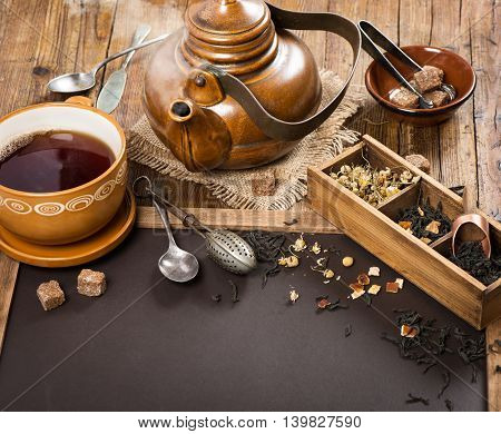 Teapot and cup with drink and black chalkboard for menu with copy space for your text.