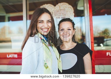 Happy teenagers friends. Two smiling teen girls outside cafe.