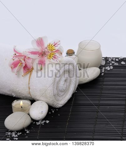 Spa setting with candle on towel ,stones on mat