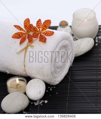 Spa setting with candle, towel on mat