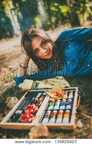 Cute artistic teen girl painter with her paint tubes and color pallet relaxing on grass on autumn day. Beautiful tennage young woman lying on grass