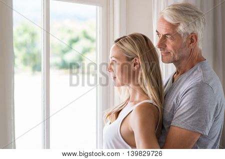 Serene mature couple looking outside the window. Senior couple thinking the future in the morning time. Happy smiling man embracing from behind his young wife and thinking about the retitrement.