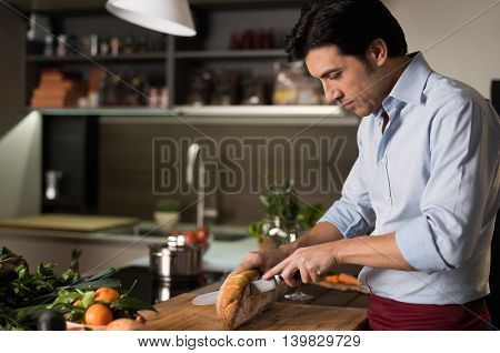 Mature man slicing bran bread on a cutting board. Man cutting a freshly baked bread. Latin man cutting a crusty homemade loaf of whole gram bread with a knife in kitchen.