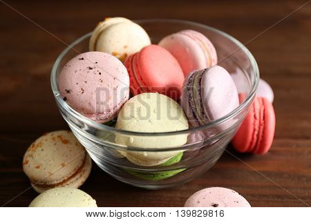 Colorful tasty macaroons in glass bowl on wooden background