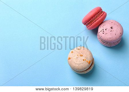 Tasty colorful macaroons on light blue background