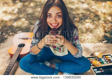 Happy smiling teen girl holding a cupcake outdoors. Artistic creative hipster with Brownie sitting on blanket on autumn day.