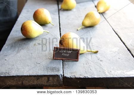 Juicy flavorful pears on a wooden table and text healthy food
