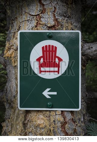 Red Chair Directional Sign posted on tree