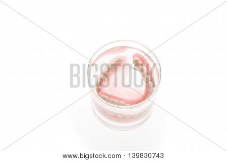 Denture in glass of water on white background