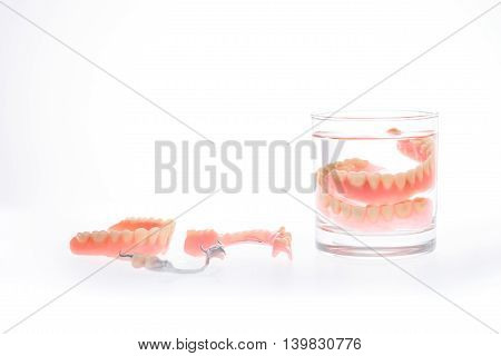Dentures in glass of water on white background