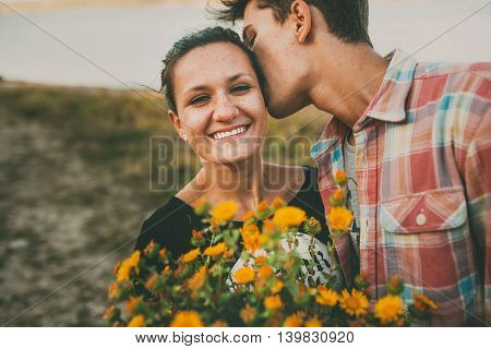 Happy teenage girl being kissed by her boyfriend outdoors. Happy relationship. Lifestyle. Feelings. Love.
