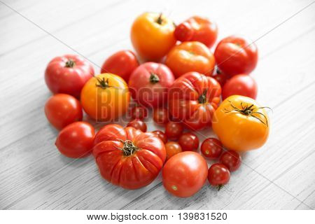 Heart shape of different tomatoes on light wooden background