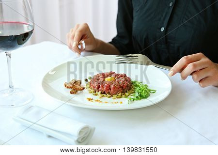 Woman eating tasty steak tartar
