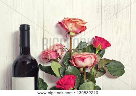 Bottle of wine and roses on a wooden background