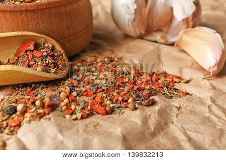 Mixed spices in wooden scoop on parchment